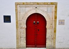 Red Tunisian door, special colour. Red Tunisian door with arabic writing details,  in the old medina, traditional nail door Royalty Free Stock Photography