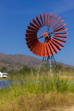 Red turbines for pump water and lagoon. Turbines for pump water use wind power stock photo