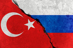 Red turkey flag on broken damage wall and half russian white red blue color flag, relationship crisis between russia and turkey Stock Photos