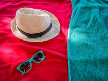 Detail of colorful beach accessoires. Red and turquoise towl with matching glasses and a straw hat Royalty Free Stock Photo