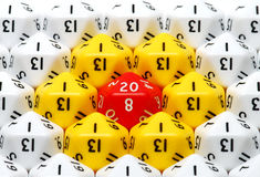 Red Twenty Sided Dice. A single red twenty in the middle of a bunch of red and yellow ones Royalty Free Stock Photo