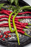 Red and two green chili peppers on old plate Stock Photography