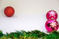 Red and two pink christmas balls, and Christmas decoration on a white background. Festive, Christmas card,red ball ,two pink balls and Christmas decorations on a Stock Photos