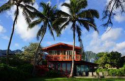 Red Two Story Beach House with tall coconut trees Stock Photos