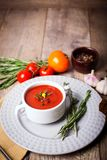 A fragrant red borscht in a white plate with a lots of vegetables on wooden background. Food concept. Royalty Free Stock Photo