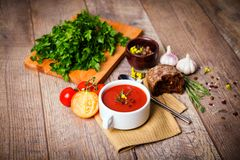 A fragrant red borscht in a white plate with a lots of vegetables on wooden background. Food concept. Stock Photos