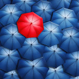 Red umbrella. Lonely red umbrella over blue umbrellas. Light coming out of umbrellas Royalty Free Stock Photos