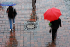 Red umbrella. DOF on pavement, motion-blur on people and umbrella Royalty Free Stock Photography