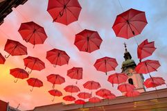 Red Umbrella Art Display At Sunset. Colorful urban art, umbrellas whimsically suspended in front of a church, at dusk Royalty Free Stock Photography