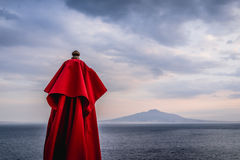Red umbrella with background of dark blue sea and Vesuvius volcano and dark cloud in sunset Sorento, south Italy royalty free stock photo