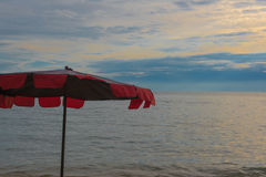Red Umbrella on the beach and Beautiful sunset and sky of the sea. Royalty Free Stock Photo