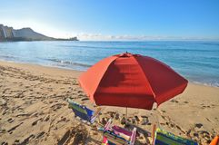 Red umbrella in beach with chairs by ocean Stock Image