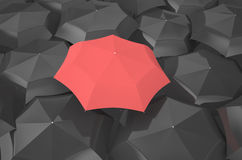 Red umbrella among black umbrellas. Red umbrella in the middle of several black umbrellas Royalty Free Stock Photo