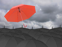 Red umbrella blown by wind and Surrounded by a black umbrella. Stock Photography