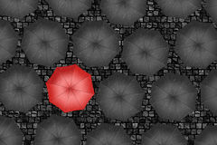 Red umbrella. Bright red umbrella among set of black umbrellas. Stock Image
