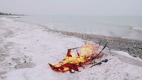 Red umbrella burns with a bright flame on the background of the sea and the sandy beach. Burning umbrella on a background of a winter beach stock footage