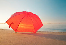 Red umbrella on calm morning seashore Stock Image