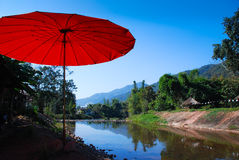 Red umbrella and clearly lake in resort Royalty Free Stock Images