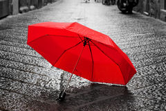 Red umbrella on cobblestone street in the old town. Wind and rain Royalty Free Stock Images