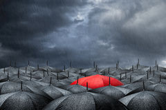 Red umbrella concept. Arm with red umbrella in mass of black umbrellas Royalty Free Stock Photography