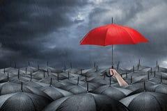 Red umbrella concept. Red umbrella in mass of black umbrellas