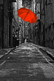 Red umbrella in a dark back street Stock Photography