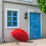 Red Umbrella in front of Retro Vintage European House Building, Narrow Street Scene. 3d Rendering. Red Umbrella in front of Retro Vintage European House Building stock image