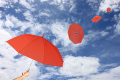 Red umbrella in hand on blue sky and cloud background. Stock Photos