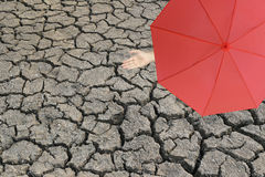Red umbrella and a hand of man standing on cracked earth and han. D protruding outside the radius to determine whether it rains or not,concept of risks in stock image