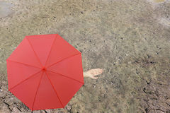 Red umbrella and a hand of man standing on soil dry pond and han. D protruding outside the radius to determine whether it rains or not,concept of risks in stock photography
