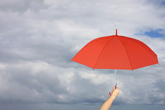 Red umbrella in hand and rain protection. Stock Photo