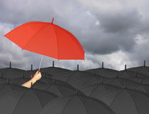Red umbrella in hand and Surrounded by a black umbrella. Royalty Free Stock Photography