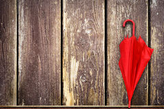 Red umbrella leaning against grunge timber fence Stock Image