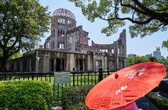Red umbrella of life. A lady with red umbrella in front of The Dome in Hiroshima Royalty Free Stock Image