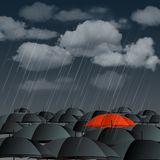 Red umbrella over many dark ones Stock Photos