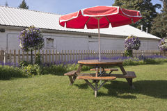 Red umbrella and a picnic bench. Royalty Free Stock Photo