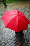 Red umbrella in rainy day. Red umbrella in rainy day on cobblestone street Stock Photo