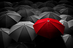 Red umbrella stand out from the crowd. Different, leader. Stock Photo