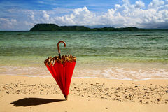 Red umbrella standing in the sand Royalty Free Stock Photos