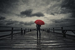 Red umbrella in storm. A woman holds a red umbrella on a fishing pier during a storm