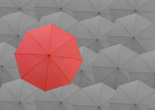Red umbrella on the top of gray umbrellas background. Stock Images