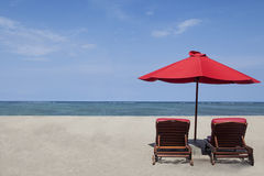 Red umbrella and two chairs Royalty Free Stock Photography