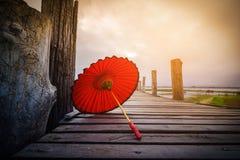 Red umbrella on U Bein bridge on sunrise in Mandalay Royalty Free Stock Photography