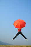 Red umbrella woman jump to Blue sky Stock Photography