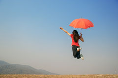 Red umbrella woman jump to Blue sky on happy day Stock Image