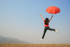 Red umbrella woman jump to Blue sky Royalty Free Stock Images