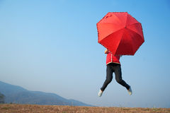 Red umbrella woman jump to sky Stock Photo