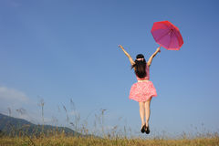 Red umbrella woman in pink dress jump to sky Royalty Free Stock Photo