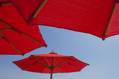 Red umbrellas on blue sky background Stock Photo