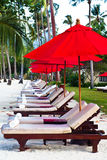 Red umbrellas and chairs on sand beach in tropic Royalty Free Stock Photos